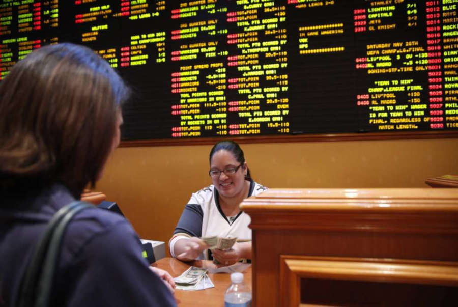 A sports betting cashier behind the counter.