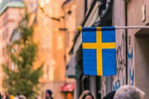 A street in Sweden with the national flag overhead.