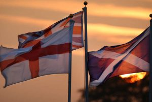 The flags of UK member countries at sunset.